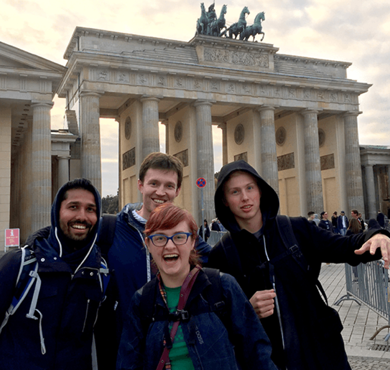 Four colleagues visiting the Brandenburg Gate in Berlin.