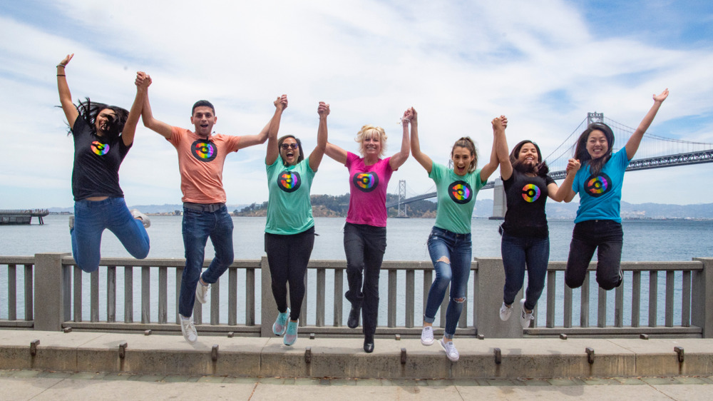 Team members in CircleCI branded t-shirts jumping in the air outside in front of the Bay Bridge in San Francisco.